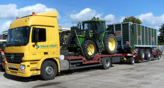 Transport maszyn rolniczych naczepą niskopodwoziowom zagłębianą.